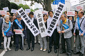Atomic bombing survivors or hibakusha and their supporters celebrate on June 29 after the Tokyo District Court accepted that six of them should be...