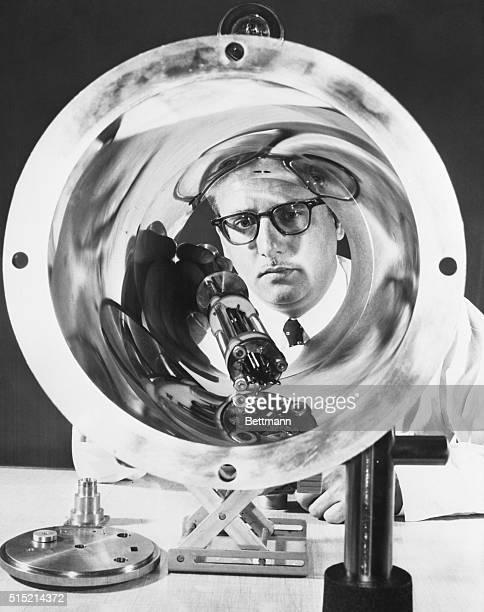 Atomic clock inventor Dr Harold Lyons is seen examining part of an atomic clock being developed by Hughes Aircraft Company for NASA