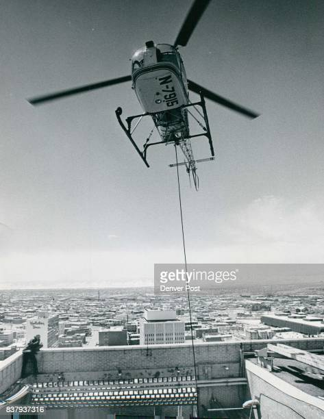 Atop Downtown Denver Building blockedoff Welton St with more material the helicopter piloted by Lert Kasdorff president of Helicopters Unlimited Inc...