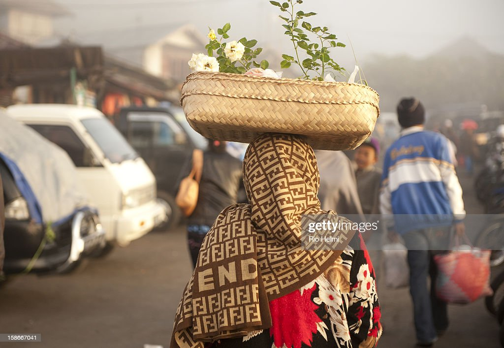 MARKET, KINTAMANI, BALI, INDONESIA - : Atough of elegance at the market - a woman in a faux designer shawl makes her way through the market in Kintaman with rose bushes in her basket..