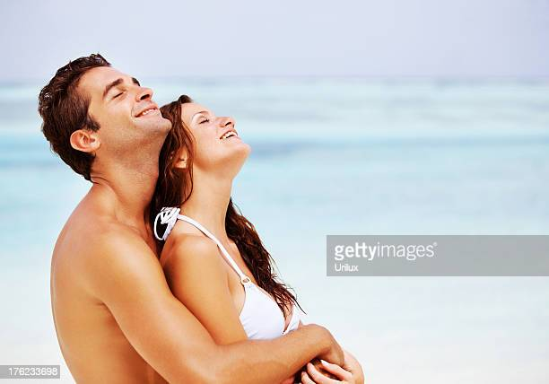 Atractive loving couple together at the beach