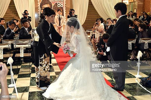 Atsuko Oka puts a bridal veil on her daughter Rie as her father Kazuyoshi Oka looks on during a wedding ceremony at the Mitsukoshi department store...