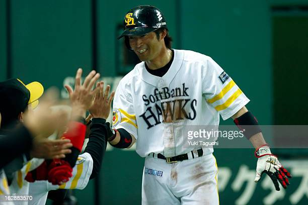 Atsushi Fukumoto of the SoftBank Hawks is greeted in the dugout after scoring a run during the World Baseball Classic exhibition game against Team...
