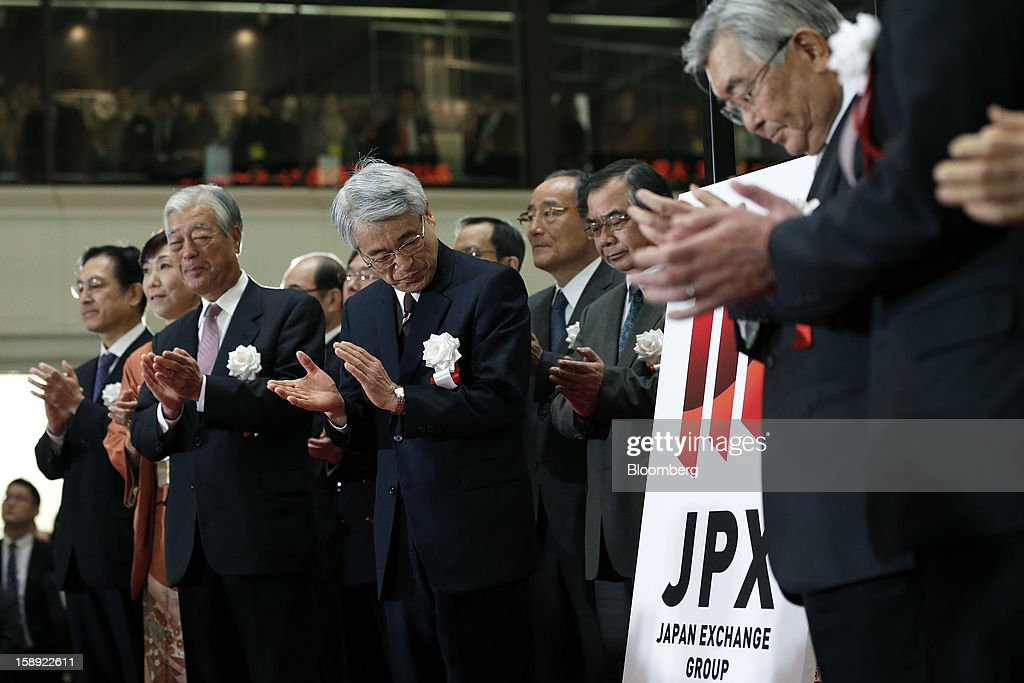 Atsushi Saito, chief executive officer of Japan Exchange Group Inc., right, and Michio Yoneda, chief operating officer, center, clap as they unveil the company's logo during a ceremony marking the first trading day of the year at the Tokyo Stock Exchange (TSE) in Tokyo, Japan, on Friday, Jan. 4, 2013. Japan Exchange, created by the merger of Japan's two biggest bourses, fell in its trading debut on the Tokyo Stock Exchange. Photographer: Kiyoshi Ota/Bloomberg via Getty Images