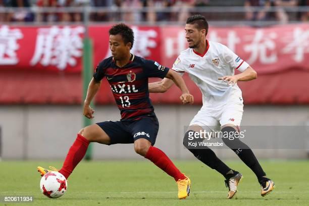 Atsutaka Nakamura of Kashima Antlers controls the ball under pressure of Sergio Escudero of Sevilla during the preseason friendly match between...