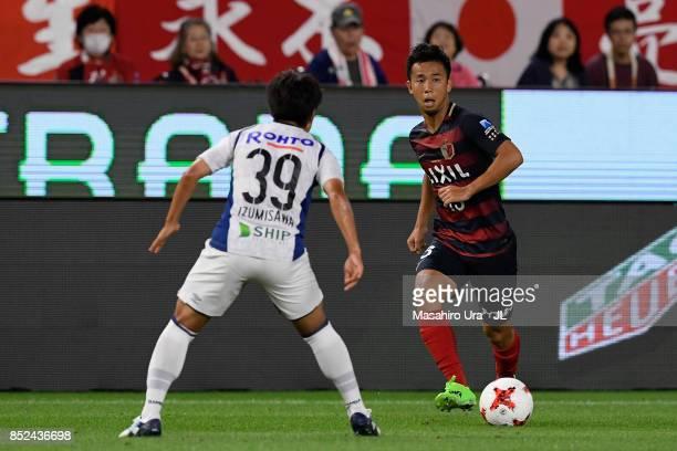 Atsutaka Nakamura of Kashima Antlers takes on Jin Izumisawa of Gamba Osaka during the JLeague J1 match between Kashima Antlers and Gamba Osaka at...