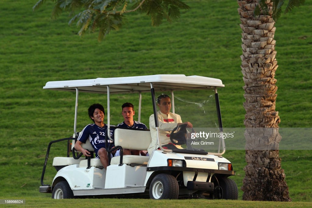 Atsuto Uchida (L) and Julian Draxler arrive in a golf cart for a Schalke 04 training session at the ASPIRE Academy for Sports Excellence on January 5, 2013 in Doha, Qatar.