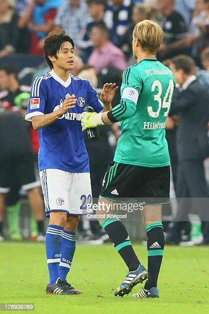 Atsuto Uchida and Timo Hildebrand of Schalke celebrate after winning the Bundesliga match between FC Schalke 04 and Bayer Leverkusen at VeltinsArena...