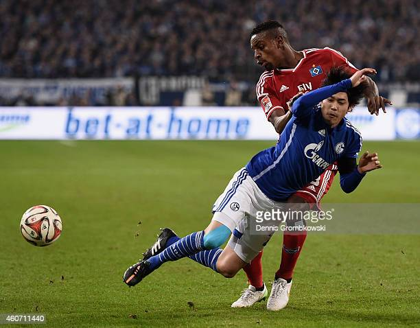 Atsuto Uchida of FC Schalke 04 is challenged by Cleber of Hamburger SV during the Bundesliga match between FC Schalke 04 and Hamburger SV at Veltins...