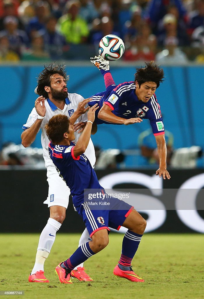 Atsuto Uchida of Japan competes for the ball with Giorgos Samaras of Greece during the 2014 FIFA World Cup Brazil Group C match between Japan and Greece at Estadio das Dunas on June 19, 2014 in Natal, Brazil.