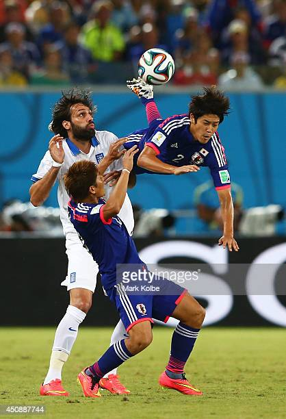 Atsuto Uchida of Japan competes for the ball with Giorgos Samaras of Greece during the 2014 FIFA World Cup Brazil Group C match between Japan and...
