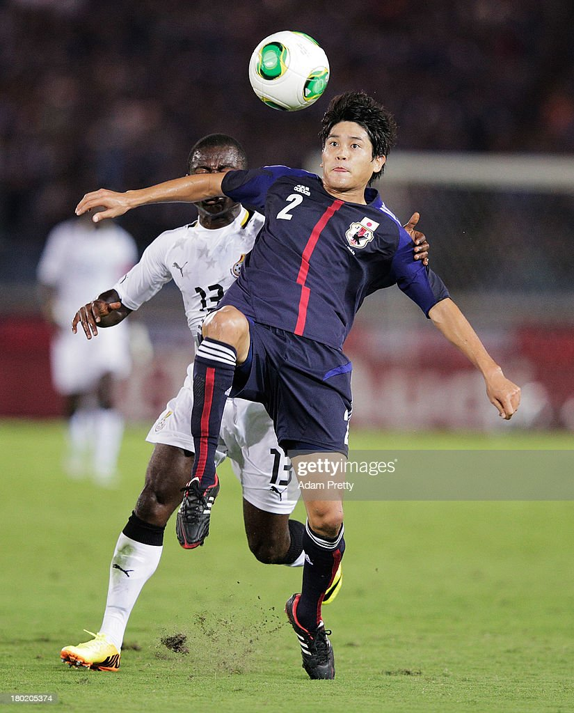 Atsuto Uchida of Japan is challenged by Frank Acheampong of Ghana during the international friendly match between Japan and Ghana at International...