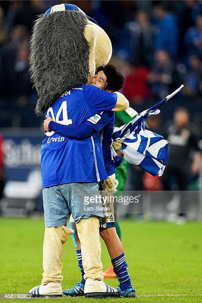Atsuto Uchida of Schalke 04 celebrates with mascot Erwin after winning the Bundesliga match between FC Schalke 04 and FC Augsburg at Veltins Arena on...