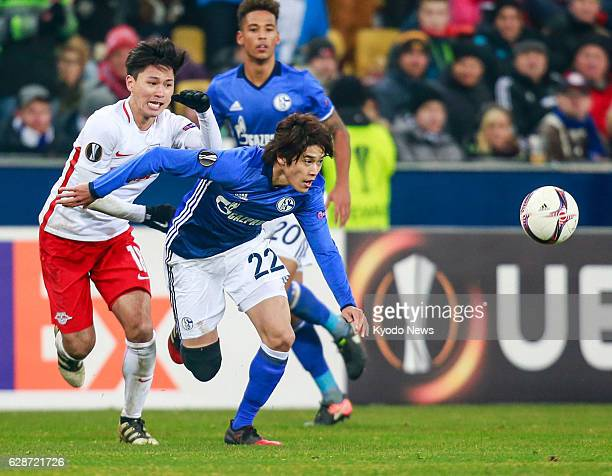 Atsuto Uchida of Schalke 04 vies for the ball with Takumi Minamino of Red Bull Salzburg during the second half of a game in the Europa League in...