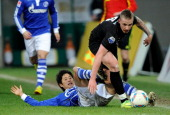 Atsuto Uchida of Schalke battles for the ball with Alexander Buettner of Arnham during the International friendly match between FC Schalke 04 and...