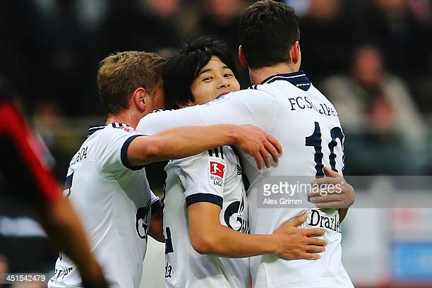 Atsuto Uchida of Schalke celebrates his team's first goal with team mates Max Meyer and Julian Draxler during the Bundesliga match between Eintracht...