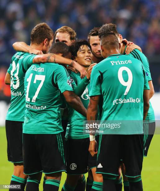 Atsuto Uchida of Schalke celebrates scoring the opening goal with team mates during the UEFA Champions League Group E match between FC Schalke 04 and...