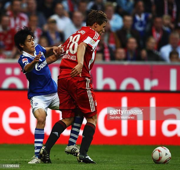 Atsuto Uchida of Schalke challenges Holger Badstuber of Bayern during the Bundesliga match between FC Bayern Muenchen and FC Schalke 04 at Allianz...
