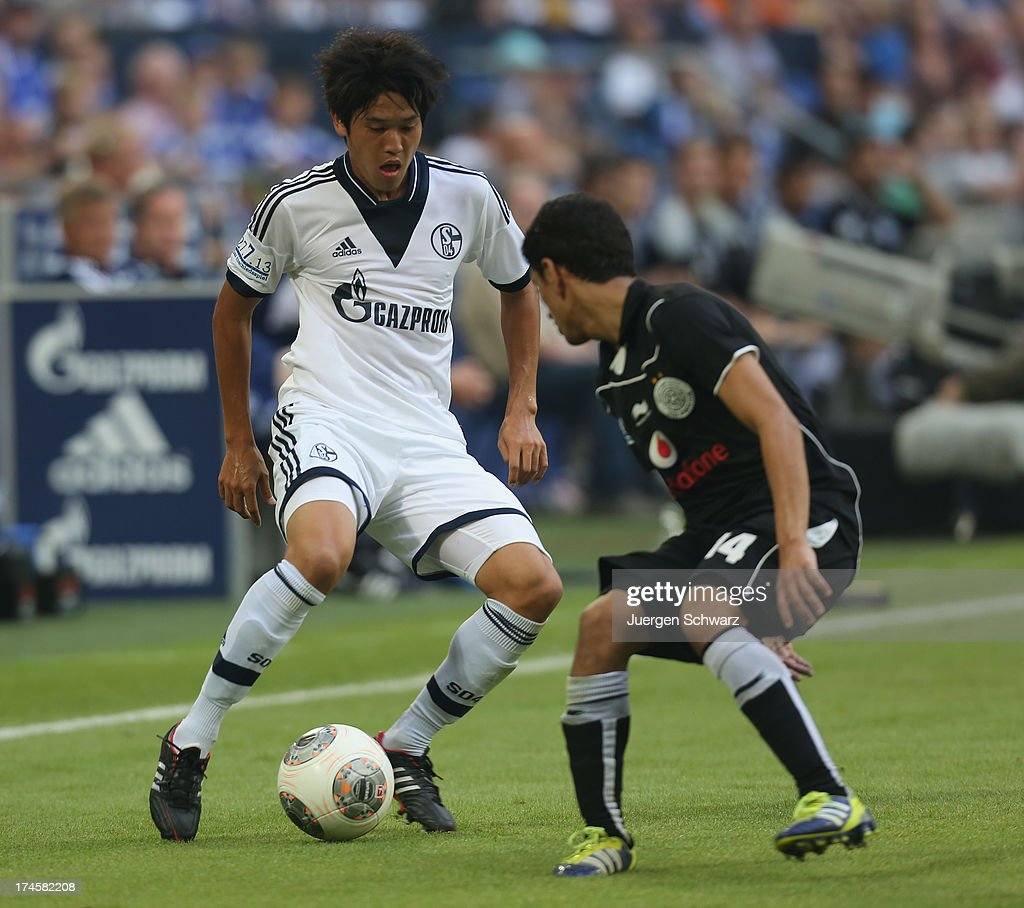 Atsuto Uchida of Schalke (L) controls the ball beside Khalfan Al Khalfan of Katar during Raul's farewell match between Schalke 04 and Al-Sadd Sports Club Katar at Veltins Arena on July 27, 2013 in Gelsenkirchen, Germany.
