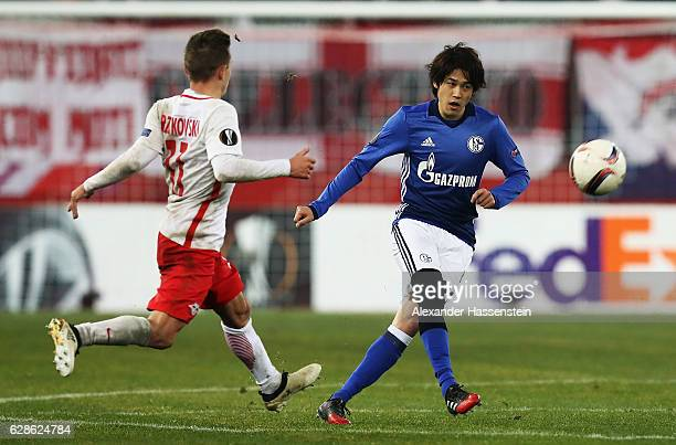 Atsuto Uchida of Schalke is challenged by Konrad Laimer of Salzburg during the UEFA Europa League match between FC Salzburg and FC Schalke 04 at Red...