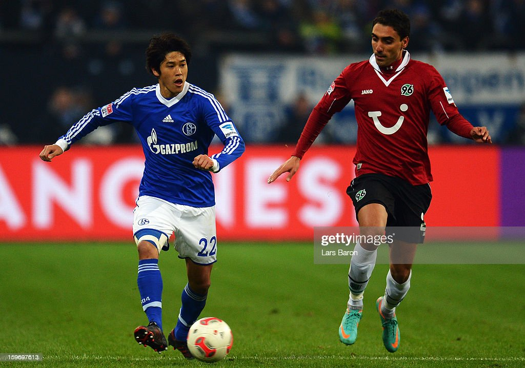 Atsuto Uchida of Schalke is challenged by Mohammed Abdellaoue of Hannover during the Bundesliga match between FC Schalke 04 and Hannover 96 at Veltins-Arena on January 18, 2013 in Gelsenkirchen, Germany.