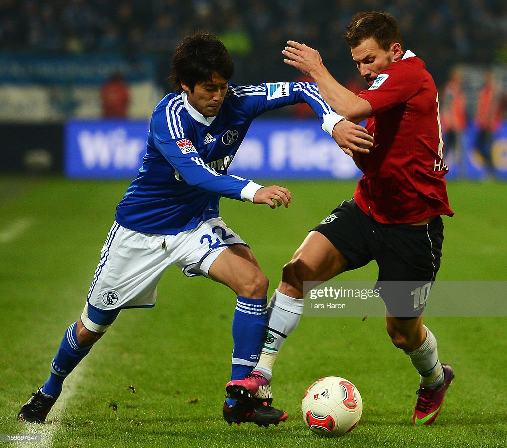 Atsuto Uchida of Schalke is challenged by Szabolcs Huszti of Hannover during the Bundesliga match between FC Schalke 04 and Hannover 96 at Veltins-Arena on January 18, 2013 in Gelsenkirchen, Germany.