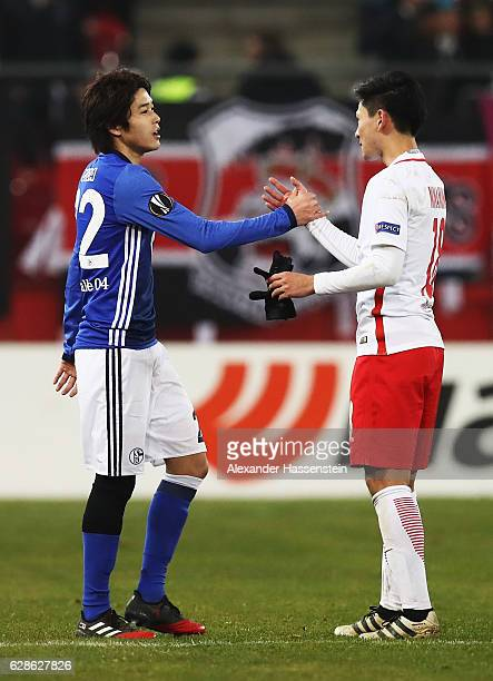 Atsuto Uchida of Schalke shakes hands with Takumi Minamino of Salzburg at the end of the UEFA Europa League match between FC Salzburg and FC Schalke...