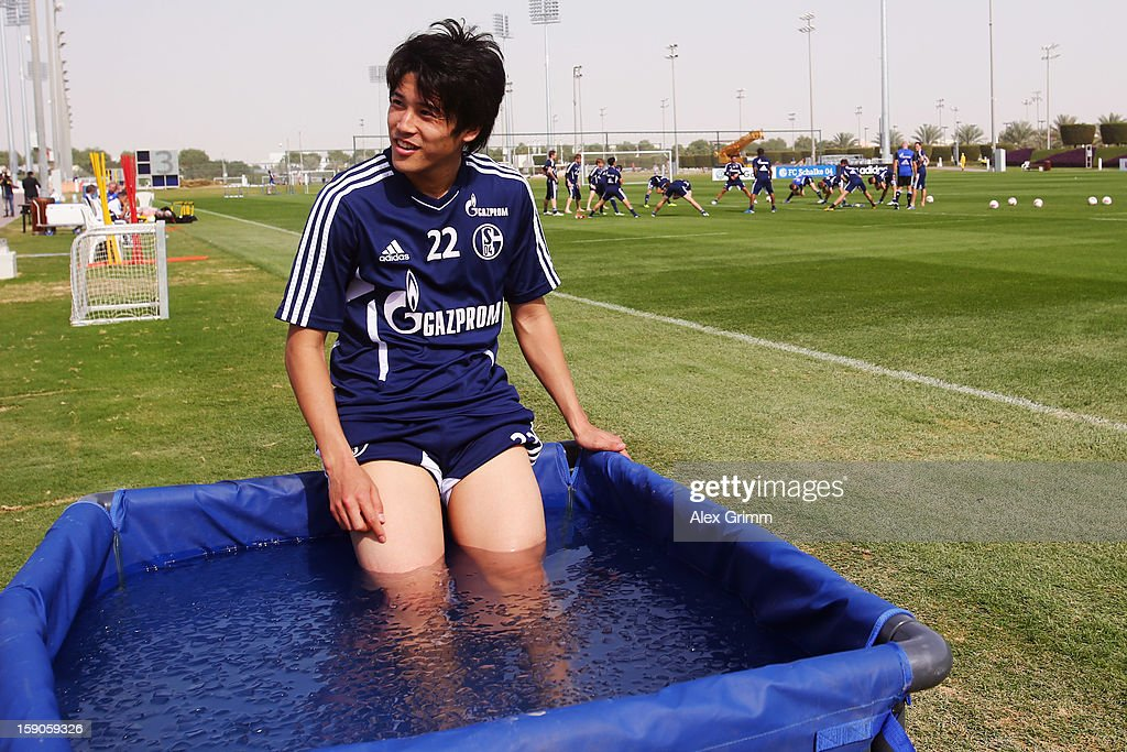 <a gi-track='captionPersonalityLinkClicked' href=/galleries/search?phrase=Atsuto+Uchida&family=editorial&specificpeople=4318608 ng-click='$event.stopPropagation()'>Atsuto Uchida</a> refreshes in an ice pool during a Schalke 04 training session at the ASPIRE Academy for Sports Excellence on January 7, 2013 in Doha, Qatar.