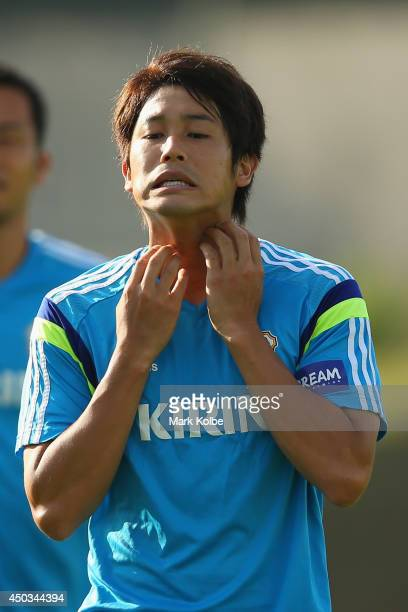 Atsuto Uchida scratches his neck during a Japan training session at the Japan national team base camp at the Spa Sport Resort on June 9 2014 in Itu...