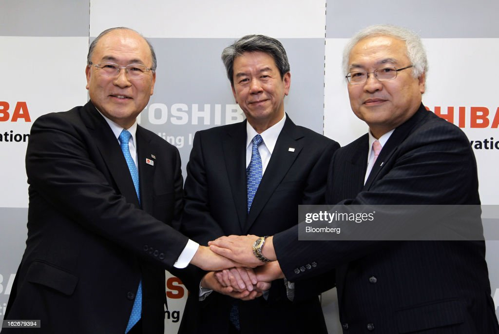 Atsutoshi Nishida, chairman of Toshiba Corp., from left, Hisao Tanaka, corporate senior executive vice president, and Norio Sasaki, president and chief executive officer, shake hands at a news conference in Tokyo, Japan, on Tuesday, Feb. 26, 2013. Toshiba, the Japanese maker of flash-memory chips, elevators and nuclear reactors, said Tanaka will take over as president in June as it tries to bolster growth from energy and chip operations. Photographer: Junko Kimura/Bloomberg via Getty Images