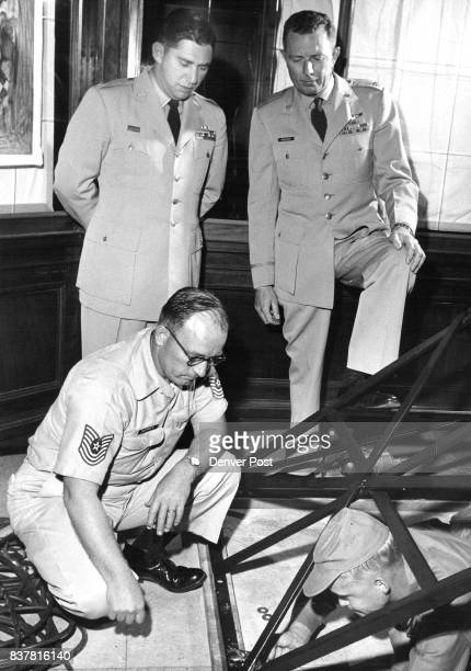Attaching the base for the 63foot replica of the Eiffel Tower being erected by Lowry Air Force Base personnel in the lobby of the Brown Palace Hotel...