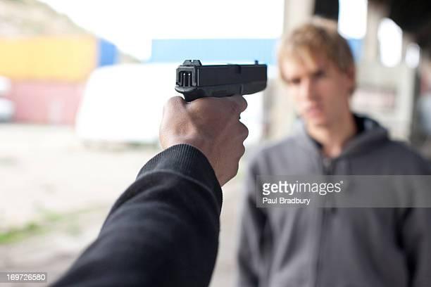 Attacker pointing gun at man