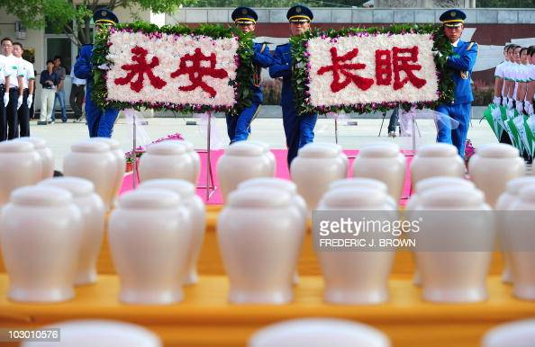Attendants approach a table filled with biodegradable urns while carrying a floral display with characters meaning 'rest in peace forever' during a...