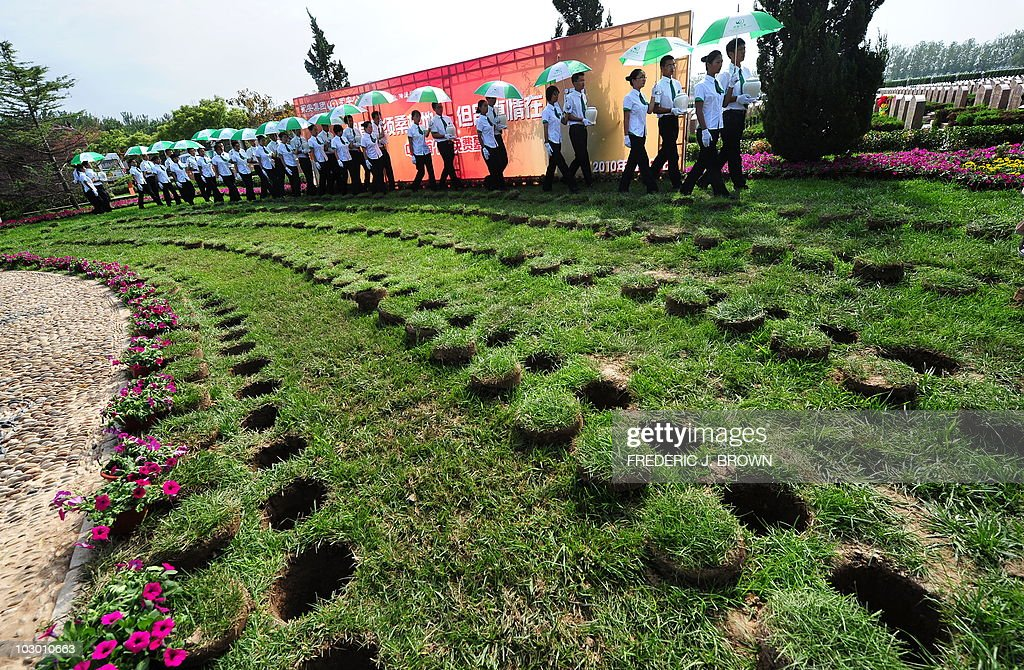 Attendants carry biodegradable urns to be placed in their respective hole in the ground during a procession at a cemetery in Tianjin northern China...