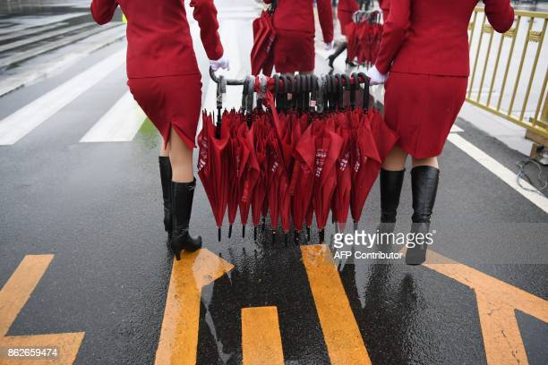 Attendants carry umbrellas back to their buses after accompanying delegates to the Great Hall of the People before the opening ceremony of the 19th...