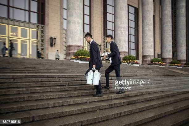 Attendants carrying flasks and cups climb a flight of steps to the Great Hall of the People after the opening ceremony of the 19th National Congress...