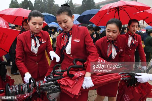 Attendants collect umbrellas after accompanying delegates to the Great Hall of the People before the opening ceremony of the 19th Communist Party...