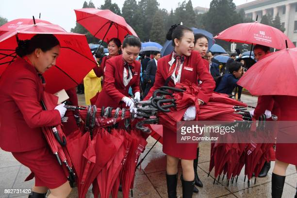 Attendants collect umbrellas after accompanying delegates to the Great Hall of the People for the opening ceremony of the 19th Communist Party...