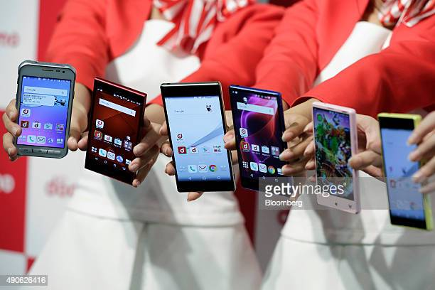 Attendants display NTT Docomo Inc's new smartphones from left Galaxy Active neo smartphone manufactured by Samsung Electronics Co Arrows smartphone...
