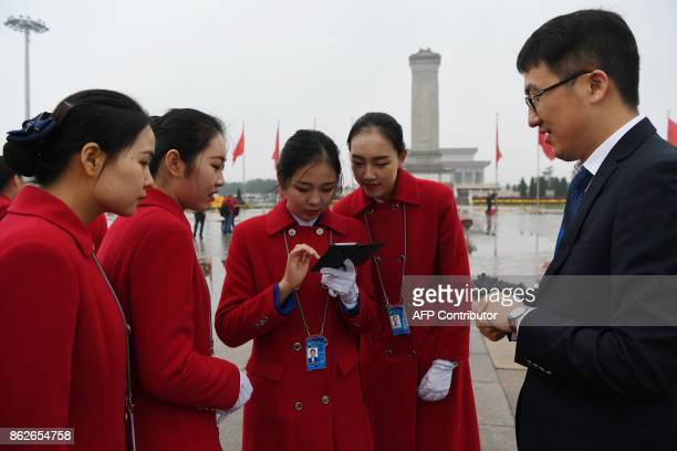 Attendants look at photos they took in Tiananmen Square as they wait for delegates during the opening ceremony of the 19th Communist Party Congress...