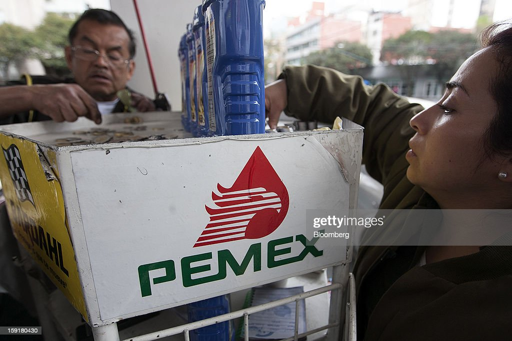 Attendants make change at a Pemex station in Mexico City, Mexico, on Tuesday, Jan. 8, 2013. Mexico's government is speeding up the removal of subsidies on gasoline and increasing local unleaded gasoline prices by 11 centavos in January, according to the Finance Ministry. Photographer: Susana Gonzalez/Bloomberg via Getty Images