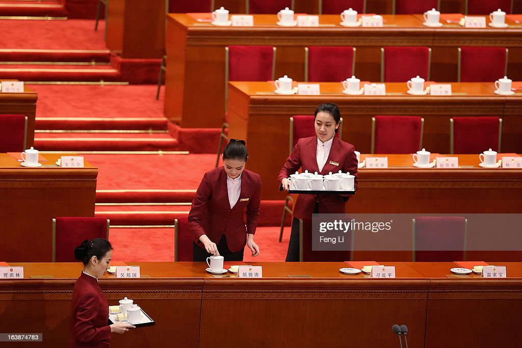 Attendants place tea cups for the top Chinese leaders at the closing session of the National People's Congress (NPC) at the Great Hall of the People on March 17, 2013 in Beijing, China. China's newly-elected president Xi Jinping pledged Sunday to resolutely fight against corruption and other misconduct in all manifestations.