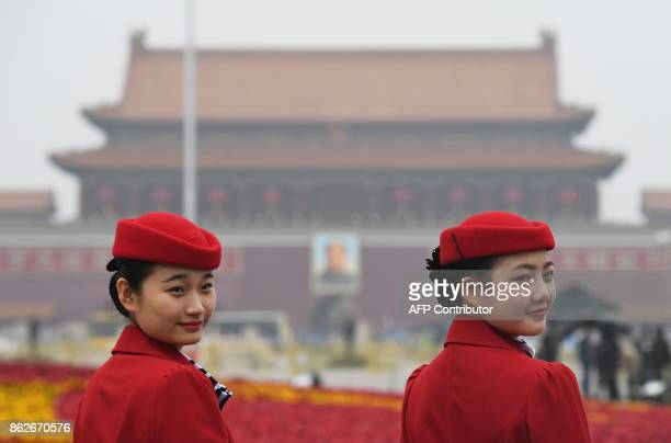 Attendants pose for photos in Tiananmen Square as they wait for delegates during the opening ceremony of the 19th Communist Party Congress in Beijing...