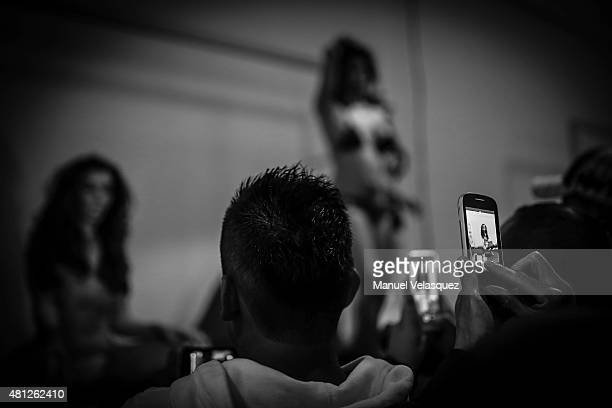 Attendants to a dancing show take pictures of nude dancers during a show as part of Expo Sexo 2015 Mexico City at Expo Reforma on July 17 2015 in...