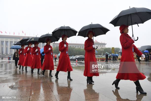 Attendants walk in Tiananmen Square as they wait for delegates during the opening ceremony of the 19th Communist Party Congress in Beijing on October...