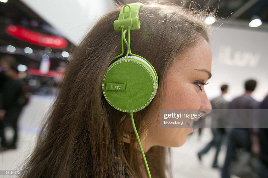 Attendee Abigail Forman demonstrates the iLuv Creative Technology 'ReF' headphones during the 2013 Consumer Electronics Show in Las Vegas, Nevada, U.S., on Wednesday, Jan. 9, 2013. The 2013 CES trade show, which runs until Jan. 11, is the world's largest annual innovation event that offers an array of entrepreneur focused exhibits, events and conference sessions for technology entrepreneurs. Photographer: Andrew Harrer/Bloomberg via Getty Images
