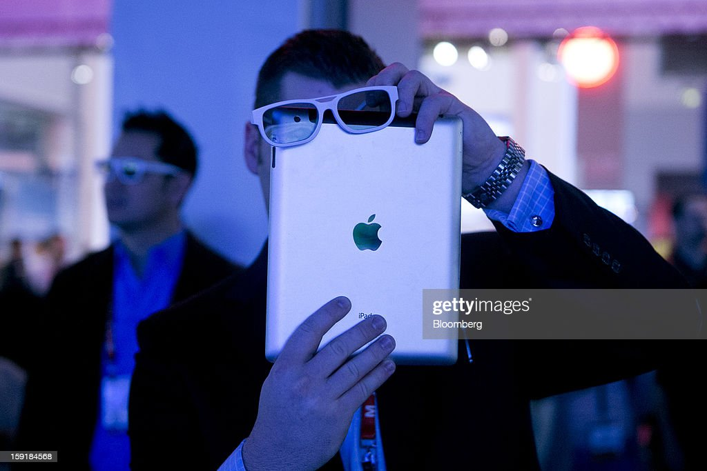 Attendee Cade Madison takes a video of the LG Electronics Inc. 3D video wall using 3D glasses over his Apple Inc. iPad during the 2013 Consumer Electronics Show in Las Vegas, Nevada, U.S., on Wednesday, Jan. 9, 2013. The 2013 CES trade show, which runs until Jan. 11, is the world's largest annual innovation event that offers an array of entrepreneur focused exhibits, events and conference sessions for technology entrepreneurs. Photographer: Andrew Harrer/Bloomberg via Getty Images