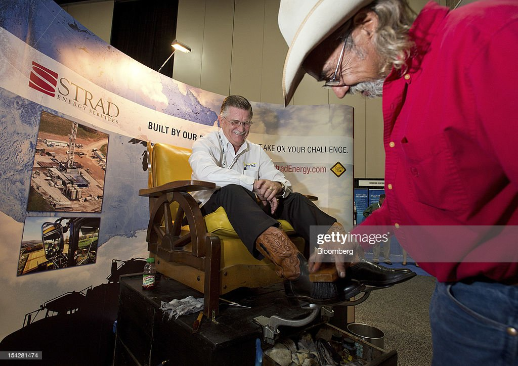 Attendee Frank Richardson, left, gets his boots shined by Norman Miller at the Strad Energy Services Ltd. booth at the DUG Eagle Ford Conference & Exhibition in San Antonio, Texas, U.S., on Monday, Oct. 15, 2012. Marathon Oil Corp., the U.S. oil and natural gas producer that spun off its refining business last year, is seeking to sell more than 96,000 net acres in the Eagle Ford formation in Texas. Photographer: Eddie Seal/Bloomberg via Getty Images *** Frank Richardson; Norman Miller