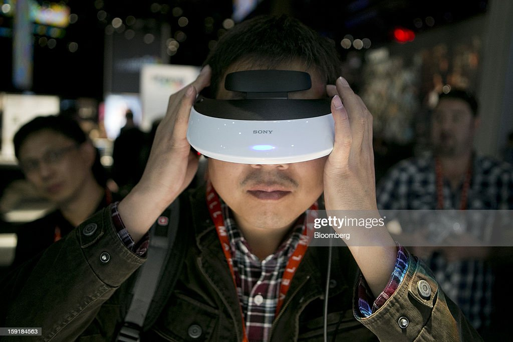 Attendee Hongqiang Bao interacts with a Sony Corp. Personal 3D Viewer headset during the 2013 Consumer Electronics Show in Las Vegas, Nevada, U.S., on Wednesday, Jan. 9, 2013. Sony Corp. is enabling its Bravia TVs, Handycam camcorders and Xperia phones to communicate with each other as Chief Executive Officer Kazuo Hirai tries to end four years of losses. Photographer: Andrew Harrer/Bloomberg via Getty Images
