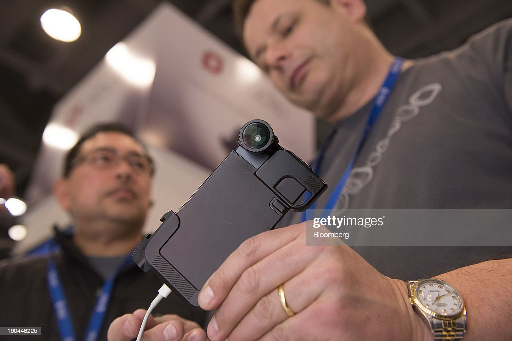 Attendee Jonathan Saniel, left, listens as Steve Muttram, business development officer at Olloclip, talks about the company's lens product for the Apple Inc. iPhone at the Macworld/iWorld conference at the Moscone Center West in San Francisco, California, U.S., on Thursday, Jan. 31, 2013. This year's conference, titled 'The Ultimate iFANEvent,' brings together attendees to celebrate Apple Inc. technology and learn more about products and services for Apple users. Photographer: David Paul Morris/Bloomberg via Getty Images